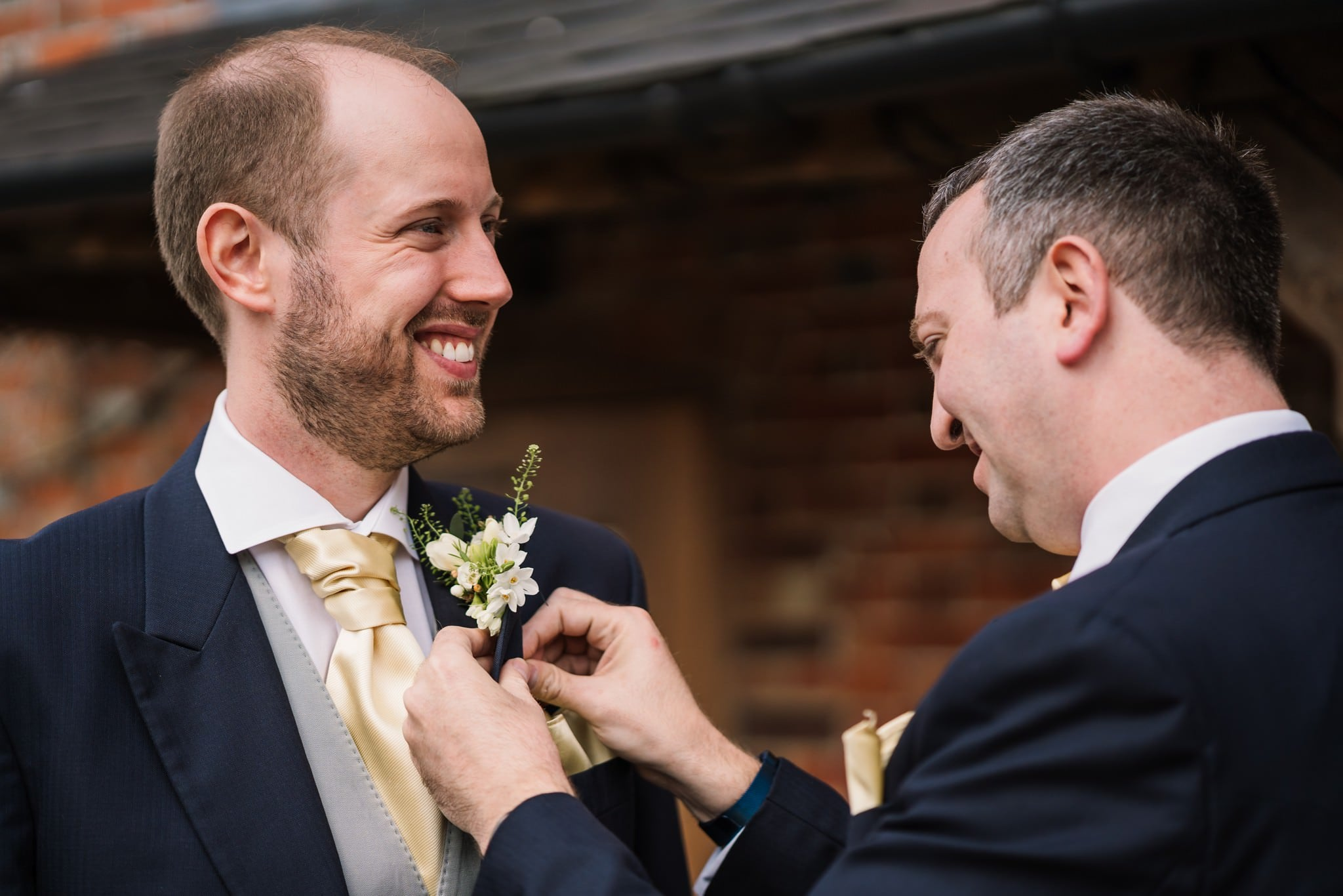 Sopley Mill groom putting on buttonhole by Dorset florist